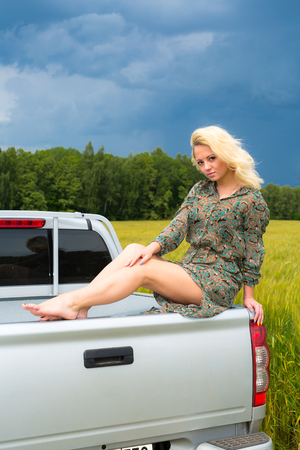sexual girl: Attractive young blonde woman sitting on car in rye field