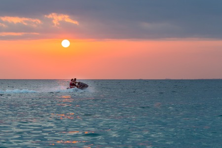 Couple riding jet ski on colorful sunset over the sea background