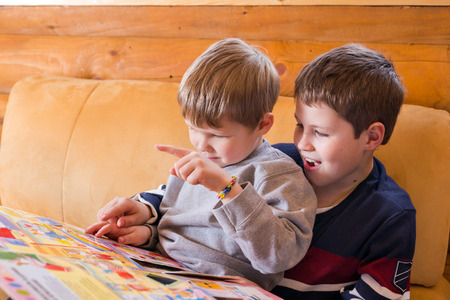 younger: Younger brother learning to read with help of elder one