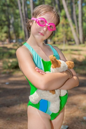 plush toy: Little girl in goggles embracing plush toy Stock Photo