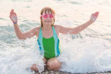 lake beach: Preteen girl with goggles having fun with sea wave Stock Photo