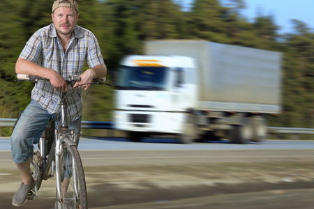 speedy: Tourist man standing on the road with a bicycle with speedy truck on background