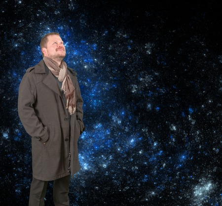 Middle-aged man in a coat and scarf looking up on starry universe background