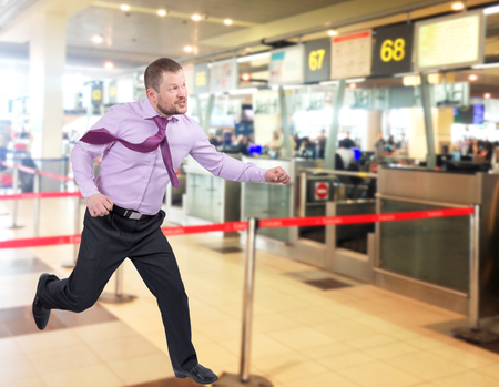 lateness: Running businessman in a hurry on airport interior background