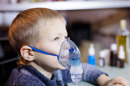litle: Litle boy sitting with nebulizer mask close up Stock Photo