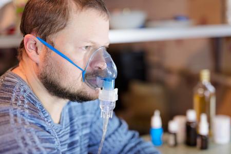 Man sitting with nebulizer mask close up view