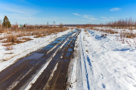 thawed: Thawed road at spring with snow and puddles Stock Photo