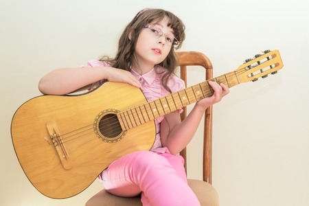 girl sit: Young little girl sitting on chair playing acoustic guitar