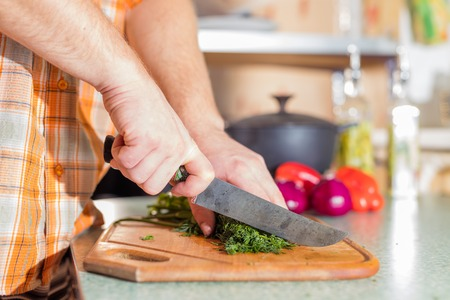 greenness: Mans hands cutting greenery and vegetables by knife