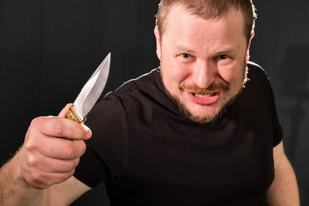 Portrait of a gangster with a knife low key Stock Photo