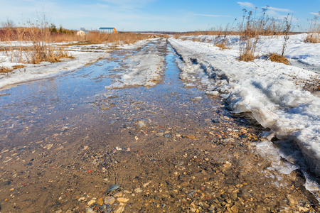 thawed: Thawed road at spring with snow and water