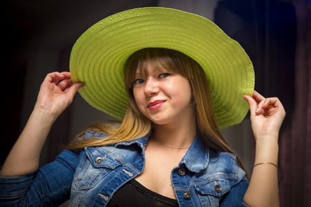 flirty: Flirty woman in green hat and blue jeans jacket