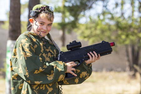 laser: Teen boy with a gun in camouflage playing laser tag Stock Photo