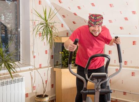 simulator: Middle aged man running on simulator at home interior