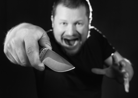 gangster: Portrait of a gangster with a knife low key Stock Photo