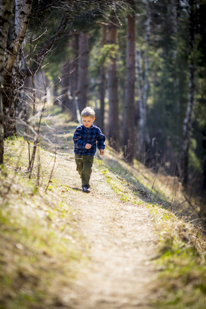 litle: Litle boy run on forest trail at sunny day Stock Photo