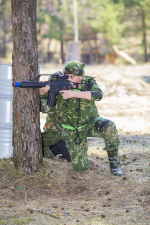 Teen boy with a gun in camouflage playing laser tag 스톡 콘텐츠