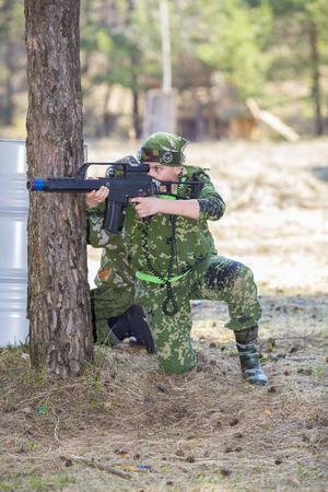 Tiener jongen met een pistool in camouflage spelen lasergames