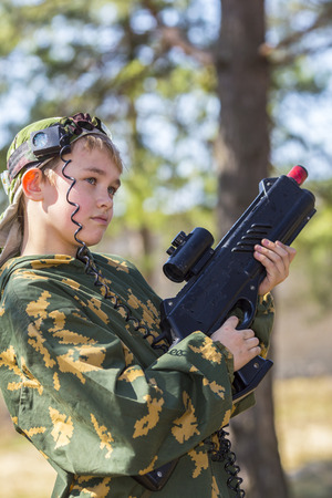 laser tag: Teen boy with a gun in camouflage playing laser tag Stock Photo