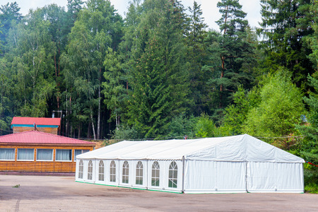 Big white banquet tent with green trees on background 스톡 콘텐츠