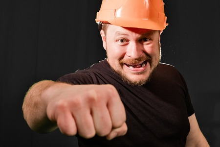 dissatisfied: Dissatisfied foreman in safety helmet emotional portrait low key