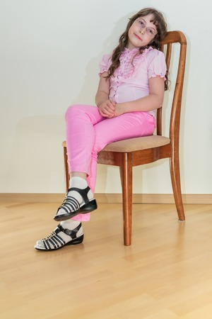 Pretty young little girl in pink jeans sitting on chair Stock Photo