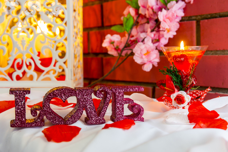 burning love: Composition with love plastic letters and candle burning