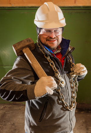 tough: Tough worker in safety helmet with iron chain and sledgehammer