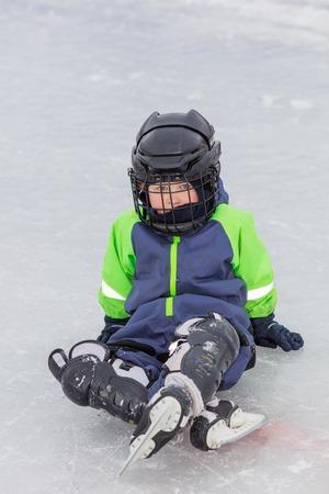 niño en patines: Niño pequeño en patines sentada en el hielo en pista de patinaje sobre hielo al aire libre