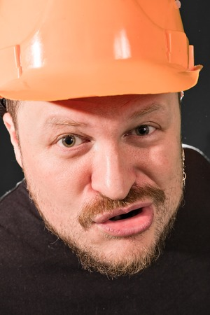 dissatisfied: Dissatisfied worker in safety helmet emotional portrait low key