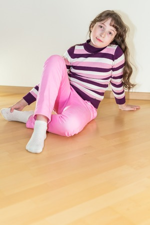 sitting on floor: Pretty young little girl in pink jeans sitting on floor