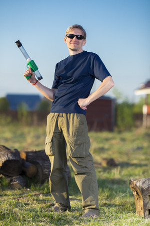 tough man: Tough man in sunglasses standing with toy gun on natural background Stock Photo