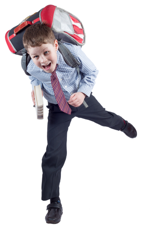 Young schoolboy with school bag in a hurry on white background