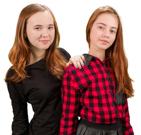 Dos muchachas adolescentes hermosas en ropa de color rojo y negro de pie en el fondo blanco