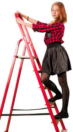 Beaytiful teen girl in checkered skirt standing on stepladder Stock Photo