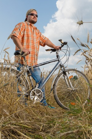 Man in cap and sunglasses standing with bicycle at the field