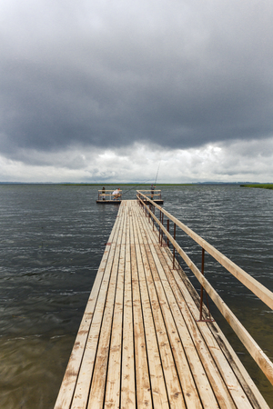 glum: Dramatic landscape with wooden pier and fishermen