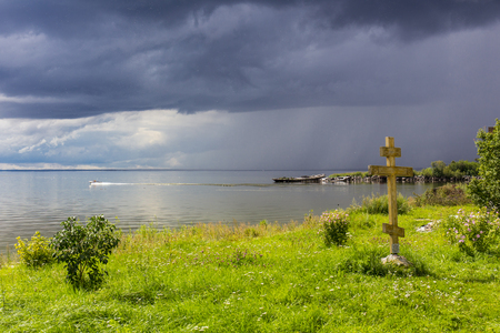 View on lake shore with grass and the cross Stock Photo