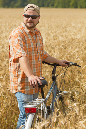 Traveller in cap and sunglasses with a bicycle at the field Reklamní fotografie