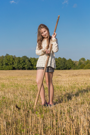 Teengirl with a scythe at summer field