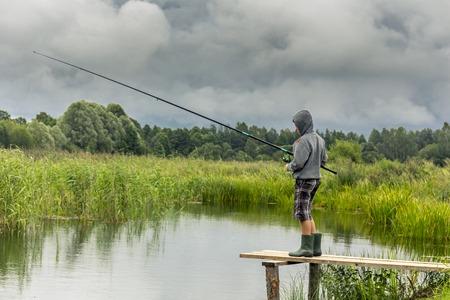 Tienerjongen die op houten pijler vissen Stockfoto
