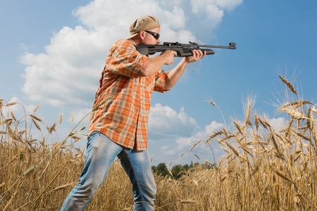 Hunter in cap and sunglasses aiming a gun at field Stock Photo