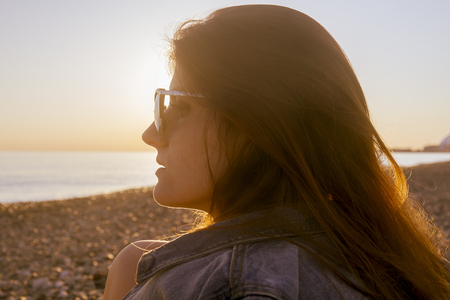 Young attractive woman on the beach at sunset time