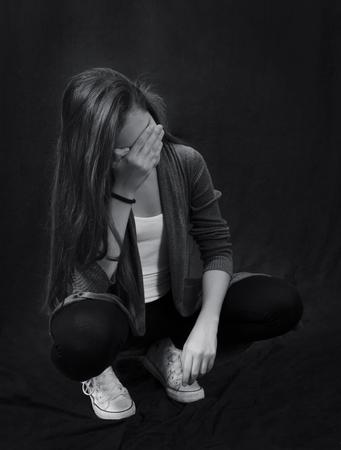 Zwart-wit close-up portret van jonge mooie meisje zitten