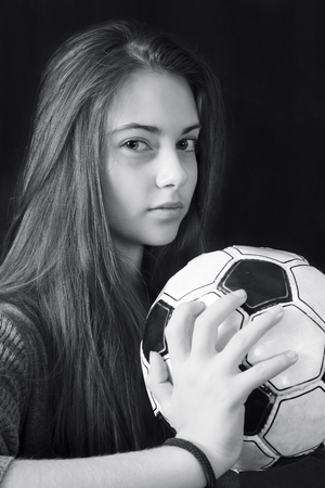 Monochrome portrait of young beautiful girl with soccer ball
