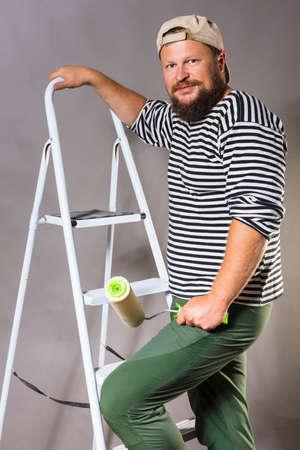 Joyful bearded craftsman with brush roller and ladder Stock Photo