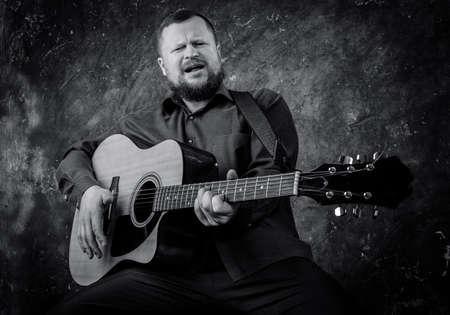 Mature musician plays acoustic guitar emotional studio portrait. Standard-Bild