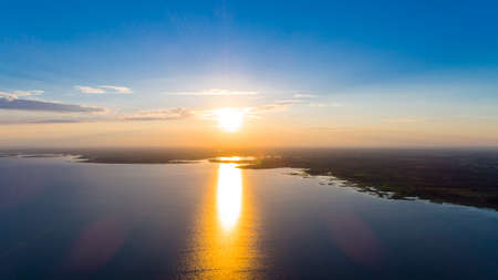 Scenic view from drone over sunset on big water and coastal line.