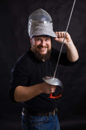 Middle aged bearded man with epee and helmet Stockfoto