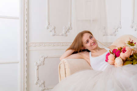 Beautiful young woman with flowers dressed in a white full wide-skirted dress sitting on the sofa Archivio Fotografico
